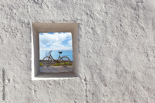 Balearic islands beach and bicycle through window