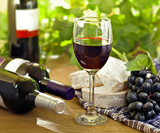 Red wine, Brie, Camembert and grape on the table, outdoor