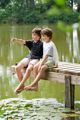 Zwei jungendliche Freunde erkunden die Umgebung am Teich