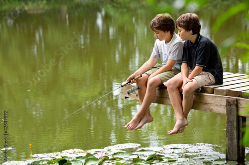 Leinwanddruck Bild Zwei jungendliche Freunde angeln am idyllischen Teich