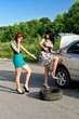 Two women are changing a tire on a road