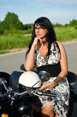 Portrait of a pretty woman on a retro motorcycle