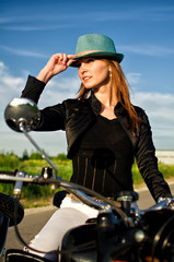 Portrait of a sexy lady in a hat sitting on motorcycle