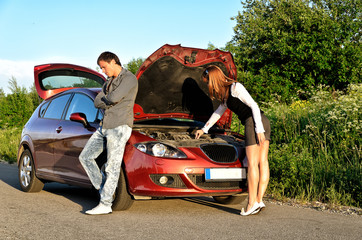 Man and woman near the broken car.
