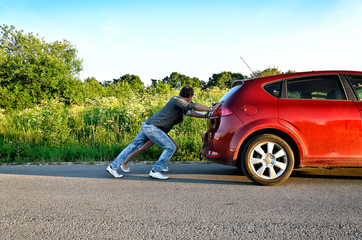 Man and woman pushing a broken car