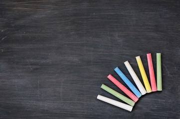 Colorful chalk on a blank smudged blackboard