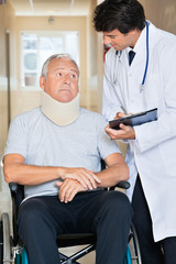 Doctor Communicating With Patient On Wheel Chair