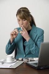 Junge Frau raucht am Arbeitsplatz