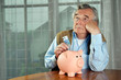 Besorgter Senior steckt Geld in Sparschwein