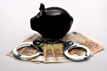Schwarzes Sparschwein steht auf 50 Euroscheinen mit Handschelle