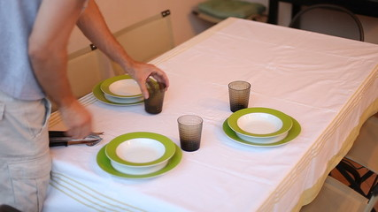 Man laying serve dishes on the table