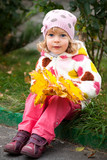 Child with bunch of yellow leaves