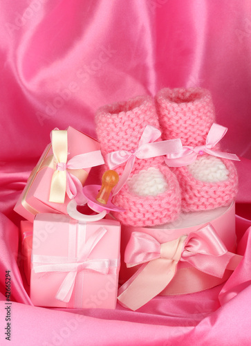 pink baby boots, pacifier, gifts on silk background.