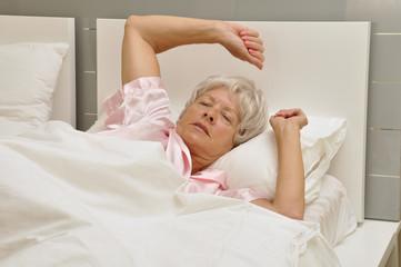 Ältere Frau im Bett wacht auf