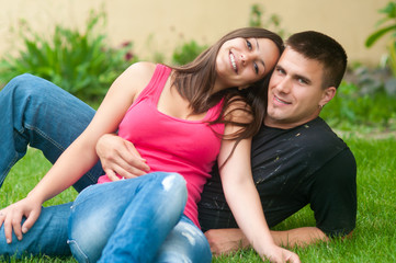 Beautiful young happy couple having fun in the grass