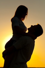 Silhouettes of young couple in love on sunny summer day