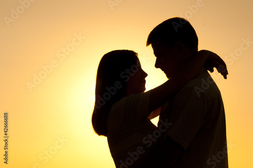Silhouettes of young couple hugging on sunny summer day