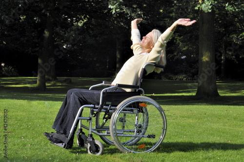 Frau im Rollstuhl steht auf Rasen