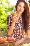 Woman holding apple. Green garden background