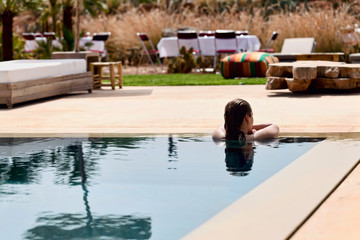 Woman relaxing on a swimming pool