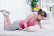 Young beautiful sportswoman exercising (doing push-up).