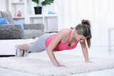 woman looking down while doing push-ups