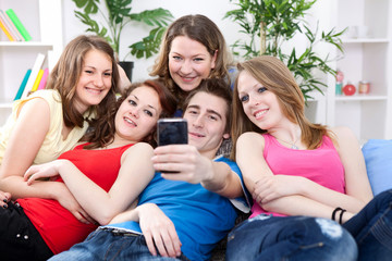 Friends taking a picture of themselves on cell phone