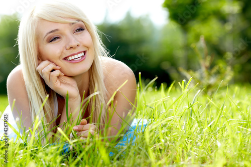 Pretty blonde girl relaxing outdoor in green grass
