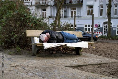 canvas print picture Obdachloser Mann schläft auf einer Parkbank