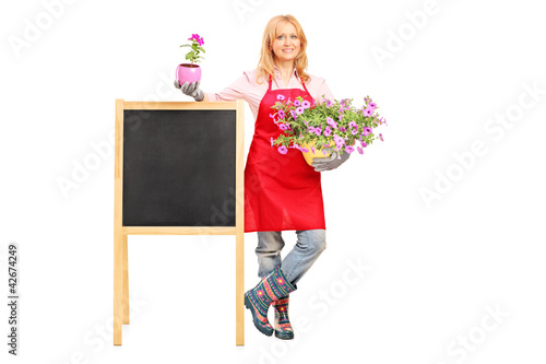 Female florist holding flowers and posing next to a board