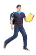 Full length portrait of a male student jumping with notebooks in