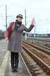 Woman in coat and cap wave goodbye on train station