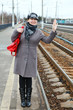 Woman in coat and cap wave goodbye standing on train station