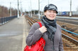 Young female standing on railway platform with red bag