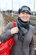 Happy fashion young woman in coat and cap with red bag