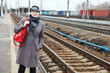 Fashion woman standing on railroad station platform