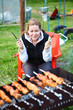 Woman with fork and knife in hands waiting for grill meat