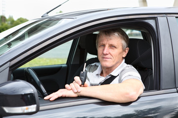 Mature male with ignition key sitting in car on driver seat