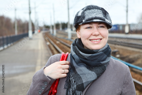 Attractive  woman in cap standing on railway station
