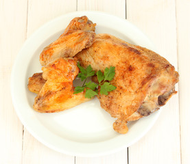 roasted chicken wings and leg with parsley in the plate
