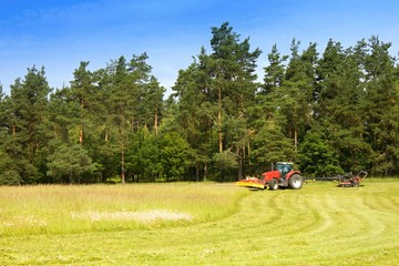 Red tractor mowing the meadow, Czech Republic