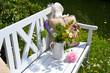 weiße Gartenbank mit Blumenstrauß