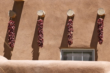 Red Chili Ristras Against Adobe Wall