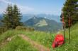 Roter Rucksack und Wanderstöcke in den bayerischen Alpen.