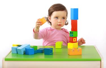 Ein Kleinkind baut einen Turm aus Bausteinen