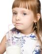 Cute little girl drinks milk using drinking straw