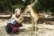 Young Caucasian girl feeding a deer in a park
