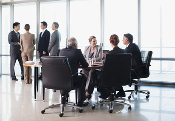 Business people meeting in separate groups in conference room