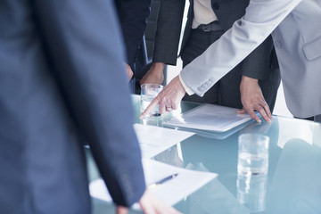 Businesswoman pointing to paperwork on table in meeting