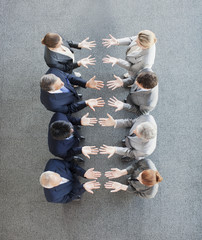 Business people standing in row with palms up